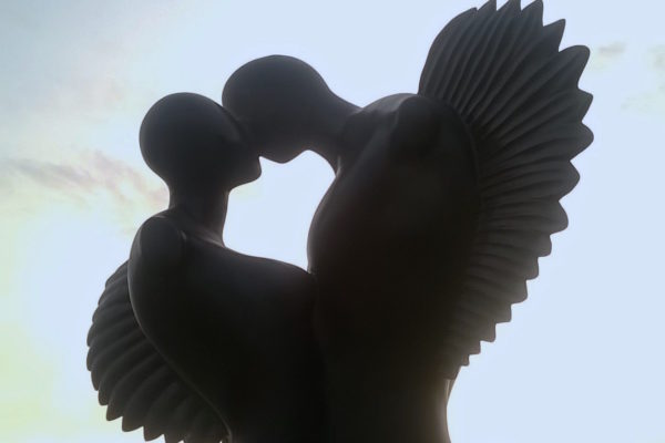 Pietrasanta: the elegant Winged Lovers sculpture in bronze with sunset sky