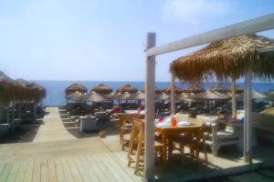 Umbrellas, chaises and terrace dining at Santorini's black sand beach