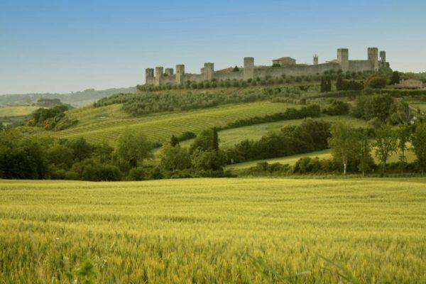 greens slopes and majestic Monteriggioni Castle