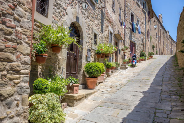 sloping street lined with stone houses in Cortona